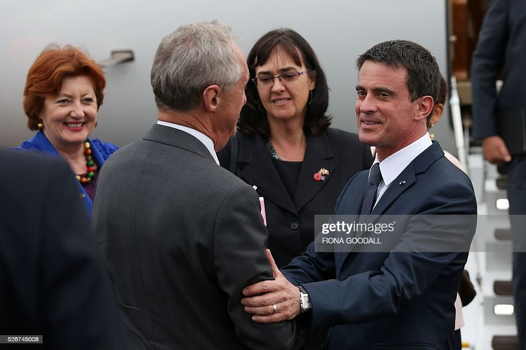 French Prime Minister Manuel Valls (R) is welcomed by New Zealand Ambassador to France James Kempers (2nd L) while New Zealand Minister for Arts, Culture and Heritage Maggie Barry looks on during Valls' arrival in Auckland on May 1, 2016. Valls arrived in New Zealand on May 1 after visiting the French Pacific territory of New Caledonia, with officials in his delegation confirming that he will detour to Australia on May 2. / AFP / Fiona Goodall