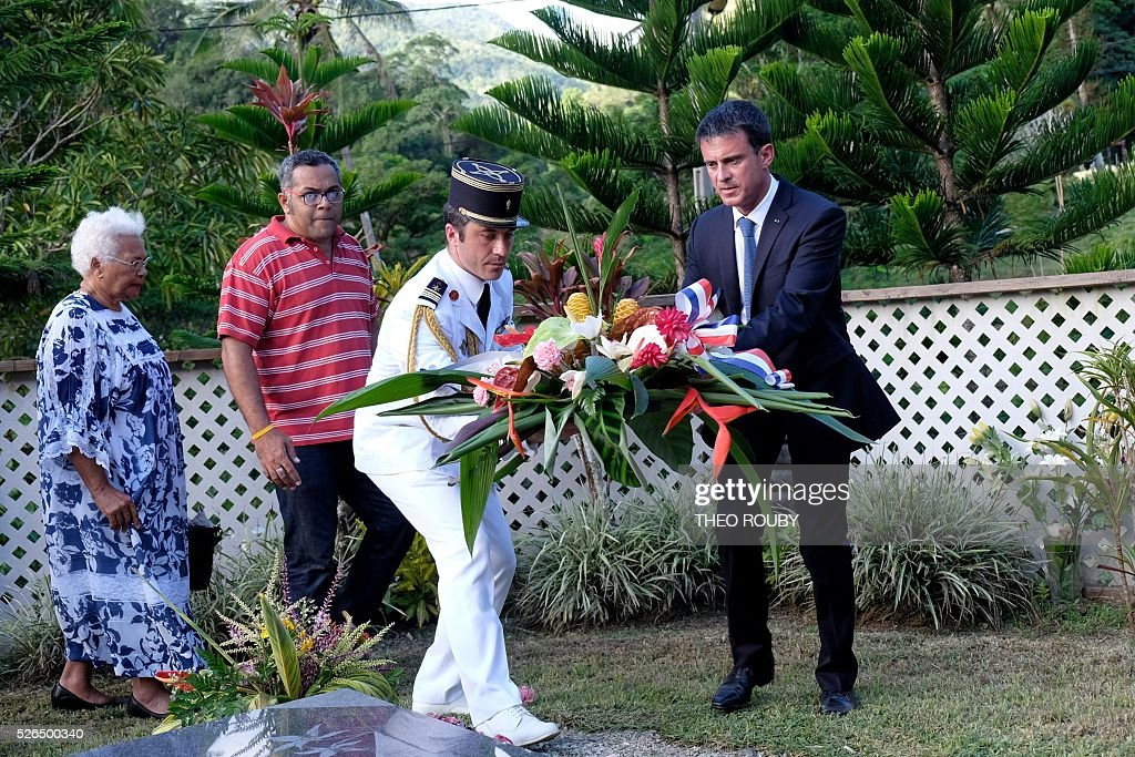 French Prime Minister Manuel Valls (R) lays a wreath at the grave of Kanak independentist leader Jean-Marie Tjibaou, along with Tjibaou's widow Marie-Claude (L) and son Emmanuel (2nd R), on April 30, 2016 in Tiendanite, near Hienghene, as part of Vall's visit to the French Pacific territory of New Caledonia. / AFP / Th��o Rouby