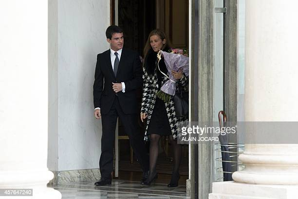 French Prime Minister Manuel Valls leaves with his wife Anne Gravoin after being awarded by French President as Grand Croix in the Ordre National du...