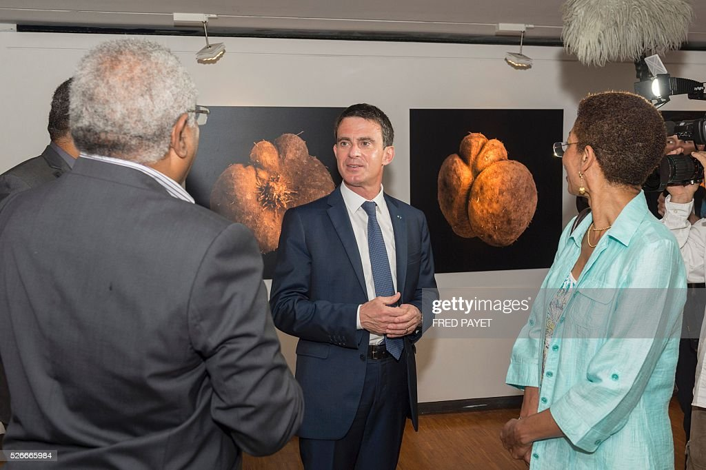 French Prime Minister Manuel Valls (C) listens as French Overseas Territories Minister George Pau-Langevin (R) looks on during a visit to the Tjibaou Cultural Centre in Noumea, the French Pacific territory of New Caledonia, on May 1, 2016. / AFP / Fred Payet