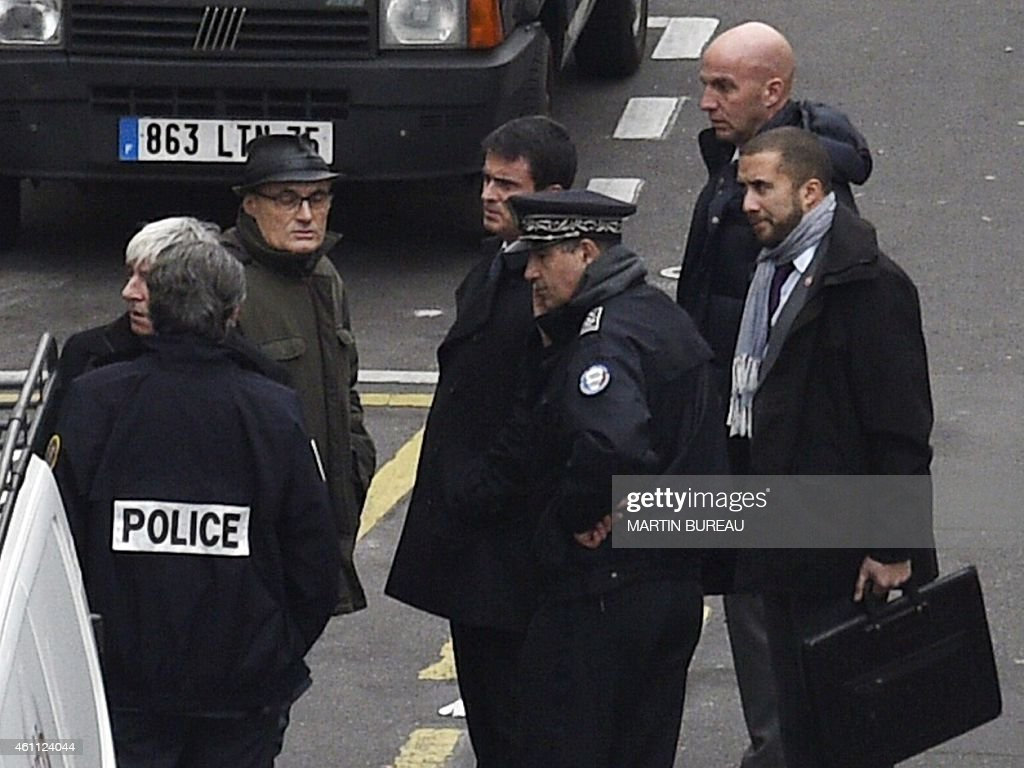 French Prime Minister Manuel Valls (C) listens to former director of the satirical political Charlie Hebdo Philippe Val (3rdL) outside of the offices of the French satirical newspaper Charlie Hebdo in Paris on January 7, 2015, after armed gunmen stormed the offices leaving 12 dead. Heavily armed gunmen shouting Islamist slogans stormed a Paris satirical newspaper office on January 7 and shot dead at least 12 people in the deadliest attack in France in four decades. Police launched a massive manhunt for the masked attackers who reportedly hijacked a car and sped off, running over a pedestrian and shooting at officers.