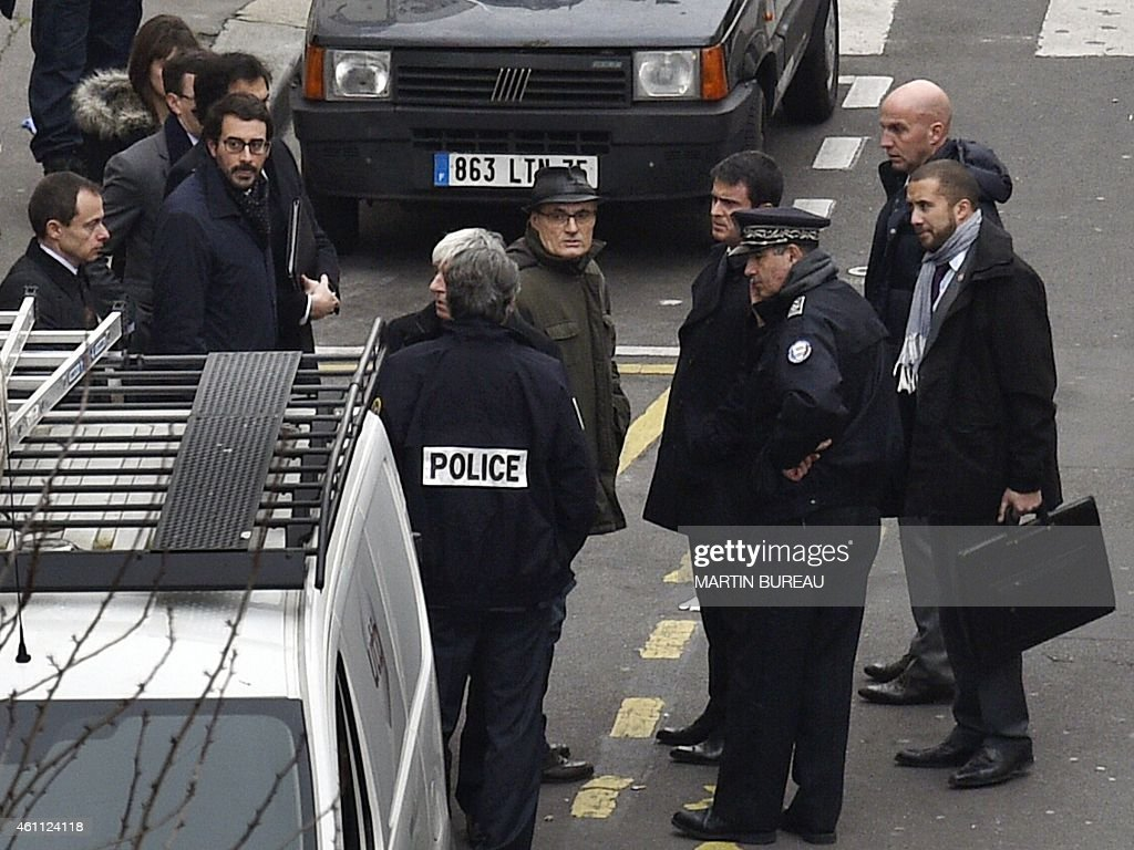 French Prime Minister Manuel Valls (4thR) listens to former director of the satirical political Charlie Hebdo Philippe Val (C) outside of the offices of the French satirical newspaper Charlie Hebdo in Paris on January 7, 2015, after armed gunmen stormed the offices leaving 12 dead. Heavily armed gunmen shouting Islamist slogans stormed a Paris satirical newspaper office on January 7 and shot dead at least 12 people in the deadliest attack in France in four decades. Police launched a massive manhunt for the masked attackers who reportedly hijacked a car and sped off, running over a pedestrian and shooting at officers.