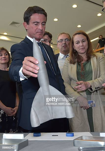 French Prime Minister Manuel Valls looks at a model rocket flanked by French Junior Minister for Digital Economy Axelle Lemaire during a visit at the...