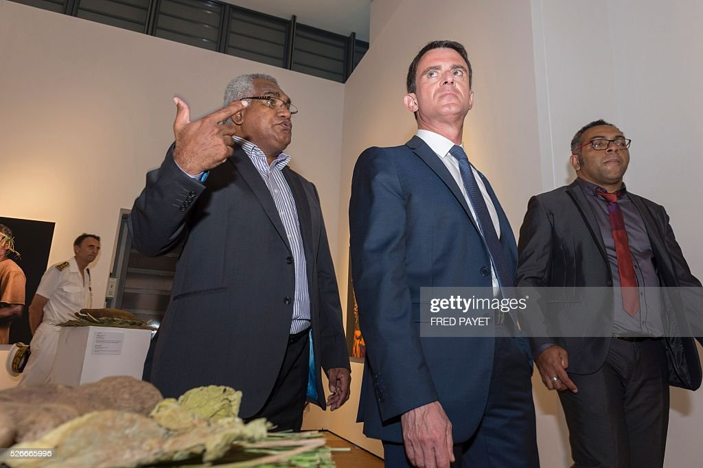 French Prime Minister Manuel Valls (C) looks at an exhibit with Emmanuel Tjibaou (R), son of Kanak independentist leader Jean-Marie Tjibaou, during a visit to the Tjibaou Cultural Centre in Noumea, the French Pacific territory of New Caledonia, on May 1, 2016. / AFP / Fred Payet