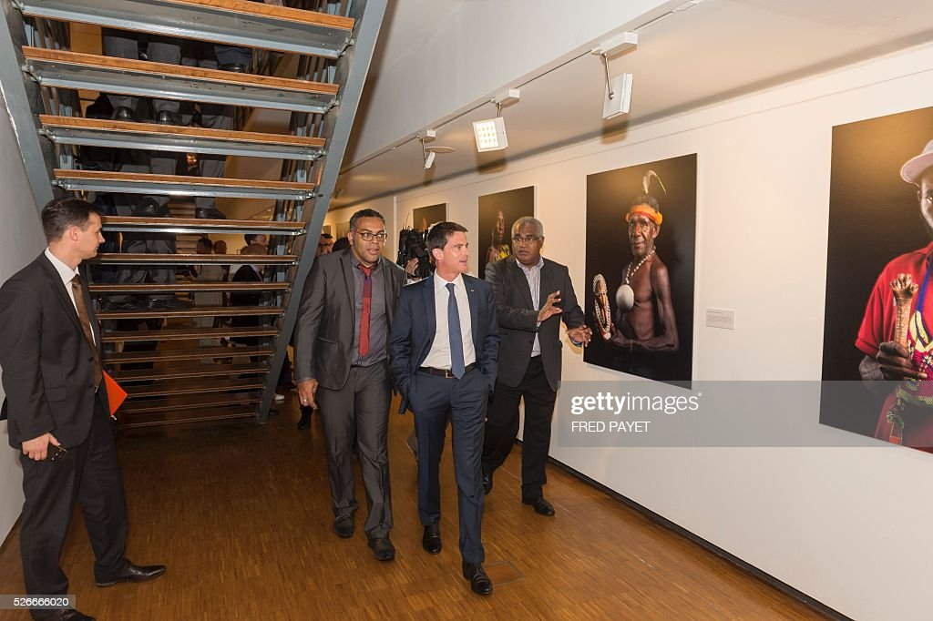 French Prime Minister Manuel Valls (C) looks at an exhibit with Emmanuel Tjibaou (2nd L), son of Kanak independentist leader Jean-Marie Tjibaou, during a visit to the Tjibaou Cultural Centre in Noumea, the French Pacific territory of New Caledonia, on May 1, 2016. / AFP / Fred Payet