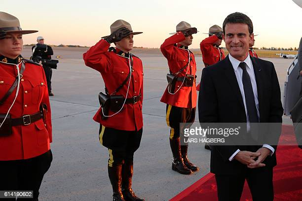 French Prime Minister Manuel Valls looks on as Royal Canadian Mounted Police officers stand at attention after he arrived at Ottawa international...