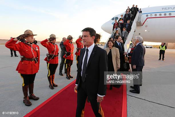 French Prime Minister Manuel Valls looks on as Royal Canadian Mounted Police officers stand at attention after they arrived at Ottawa international...