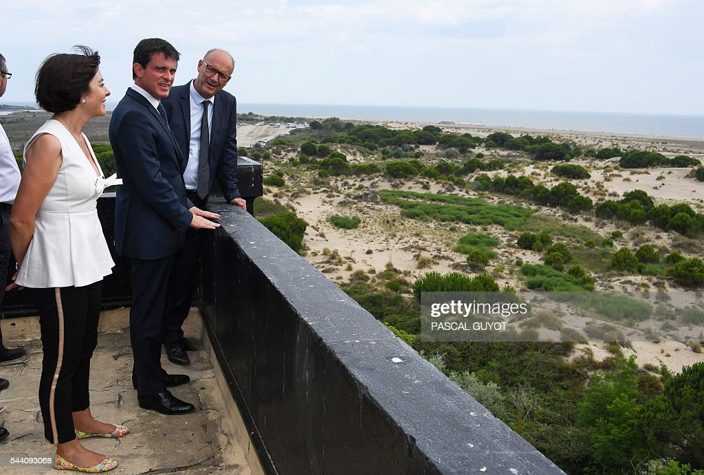 French Prime Minister Manuel Valls (C), Mayor of Le Grau-Du-Roi Robert Crauste (R) and Carole Delga, president of the regional council Occitanie (L), visit the lighthouse of Espiguette beach, southern France, on July 1, 2016. / AFP / PASCAL