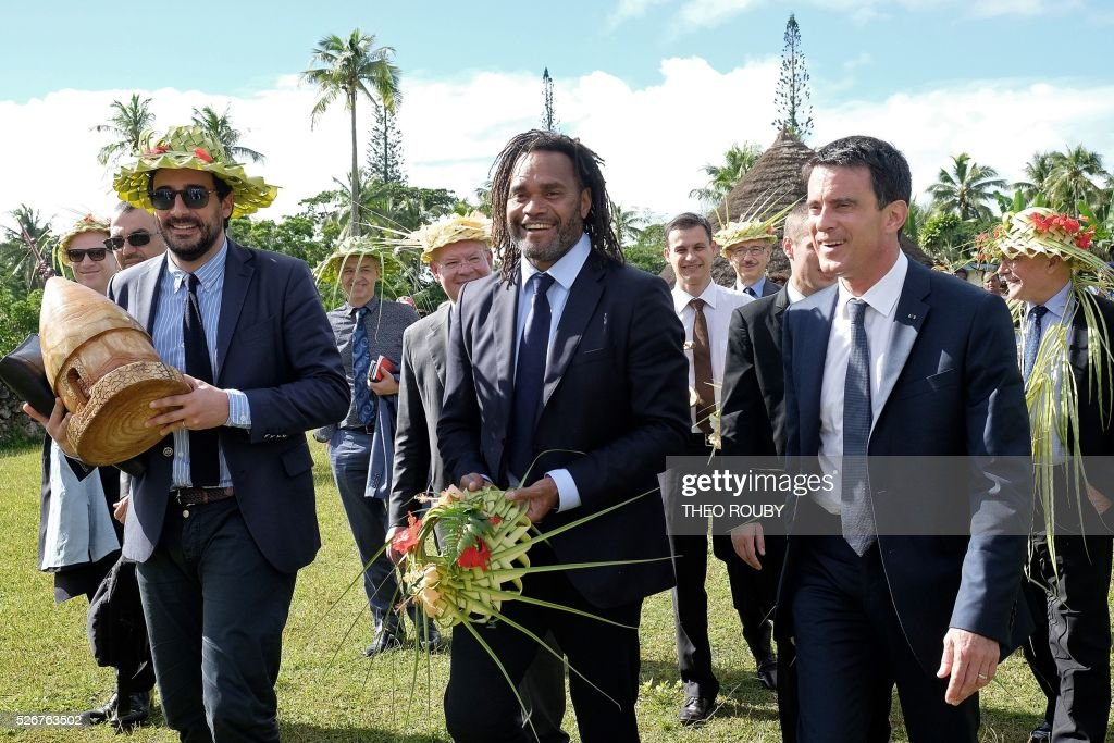 French Prime Minister Manuel Valls (R) meets with Hnatalo traditional leaders along with former French footballer Christian Karembeu (C) during a visit to the island of Lifou in New Caledonia on May 1, 2016. / AFP / Th��o Rouby