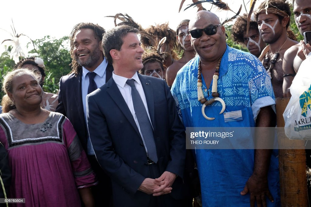 French Prime Minister Manuel Valls (C) meets with Hnatalo traditional leaders along with former French footballer Christian Karembeu (back L) during a visit to the island of Lifou in New Caledonia on May 1, 2016. / AFP / Th��o Rouby