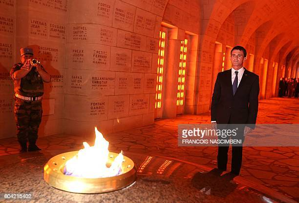 French Prime minister Manuel Valls pays his respect during a ceremony marking the 100th aniversary of the presentation to the city of the Croix de...