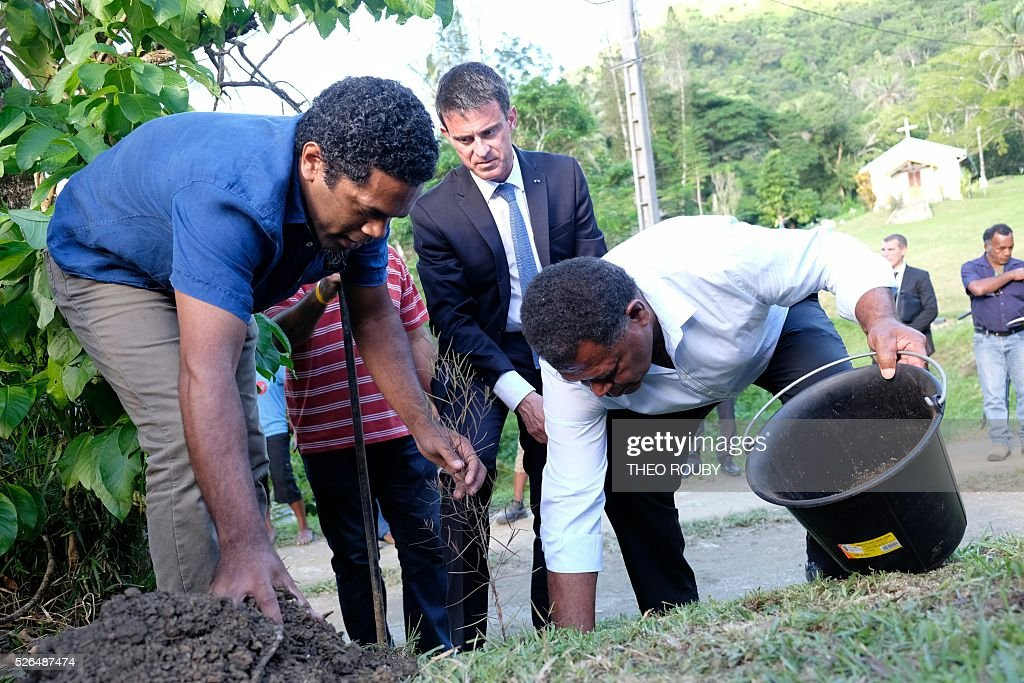 French Prime minister Manuel Valls (C) plant a tree with members of the Tiendanite tribe, on April 30, 2016 in Tiendanite, as part of his visit to the French Pacific territory of New Caledonia. The Tiendanite tribe was the tribe of Jean-Marie Tjibaou, late leader of the Kanak independence movement and politician assassinated in 1989. / AFP / POOL / Th��o Rouby