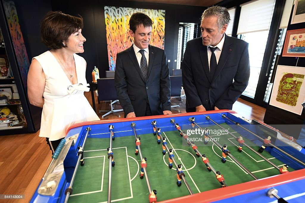 French Prime Minister Manuel Valls (C) plays with a table football next to Mayor of Montpellier Philippe Saurel (R) and Carole Delga (L), president of the regional council of Occitanie, on July 1, 2016, as they a visit in Montpellier, southern France. / AFP / PASCAL