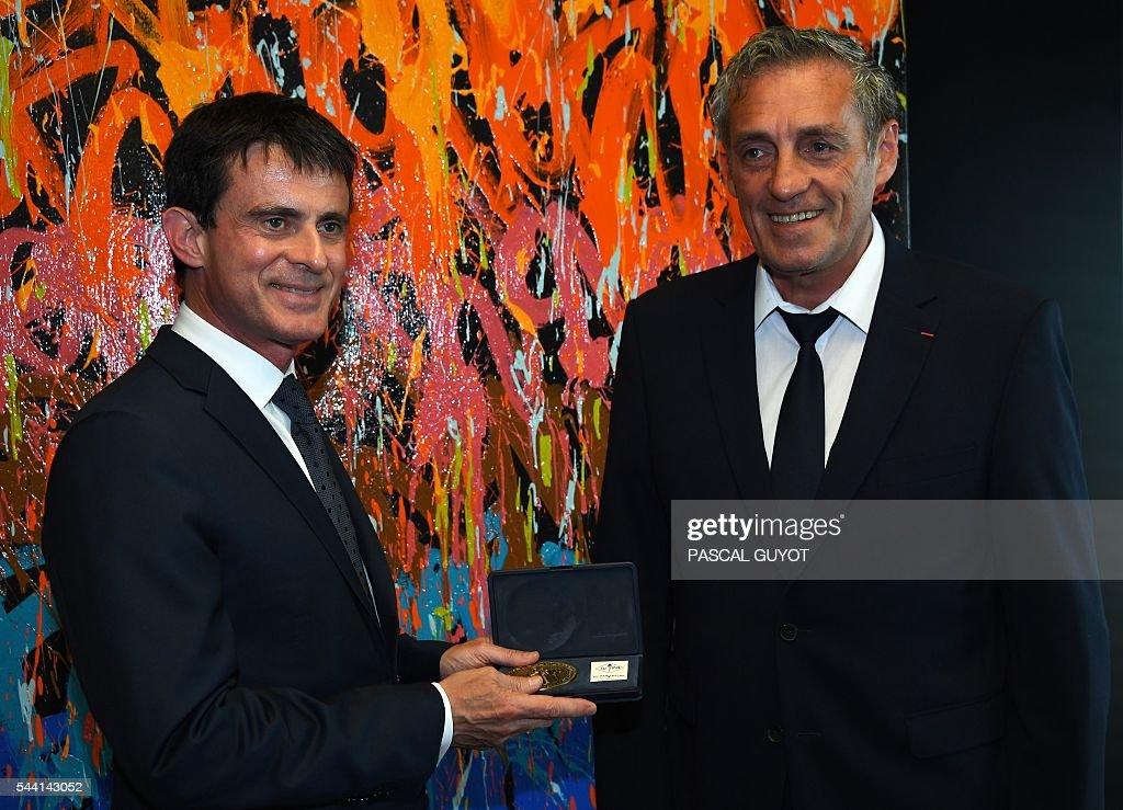 French prime minister Manuel Valls (L) poses after being awarded the medal of the city by Mayor of Montpellier Philippe Saurel (R) on July 1, 2016, during a visit in Montpellier, southern France. / AFP / PASCAL