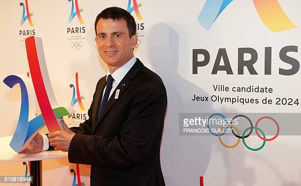 French Prime Minister Manuel Valls poses with the logo of Paris as candidate for the 2024 Olympic summer games during a press conference in Paris on...