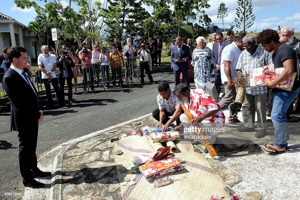 French Prime Minister Manuel Valls (L) presents a customary offering on April 30, 2016 in Kone, as part of his visit to the French Pacific territory of New Caledonia. / AFP / Th��o Rouby