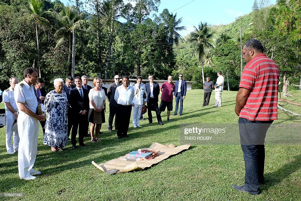 French Prime Minister Manuel Valls (3rd L) presents a customary offering to the Tiendanite tribe, represented by Emmanuel Tjibaou (R), son of Kanak independentist leader Jean-Marie Tjibaou, flanked by French Republic's High Commissioner in New Caledonia Vincent Bouvier (L), Tjibaou's widow Marie-Claude (2nd L), Isabelle Lafleur (4th L), daughter of French former deputy of New Caledonia Jacques Lafleur, and Mayor of Hienghene Daniel Gao (5th L), on April 30, 2016 in Tiendanite, near Hienghene, as part of Vall's visit to the French Pacific territory of New Caledonia. / AFP / Th��o Rouby