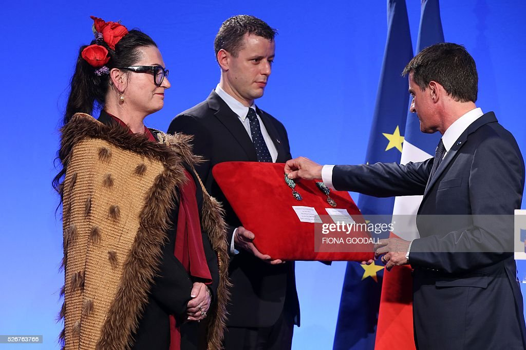 French Prime Minister Manuel Valls presents Fiona Pardington with a Ordre des Arts et des Lettres medal at a French community event at Auckland War Memorial Museum on May 1, 2016. / AFP / Fiona Goodall