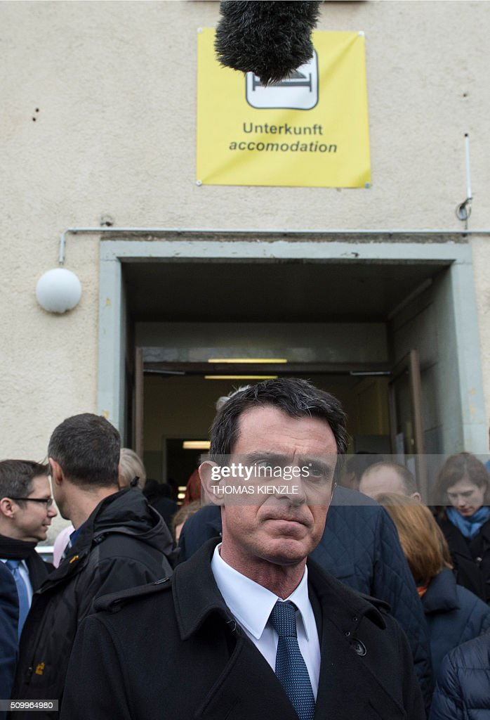 French Prime Minister Manuel Valls reacts as he leaves an accomodation in the refugee camp Bayernkaserne (Bavaria barracks) in Munich, southern Germany, on February 13, 2016. / AFP / THOMAS KIENZLE