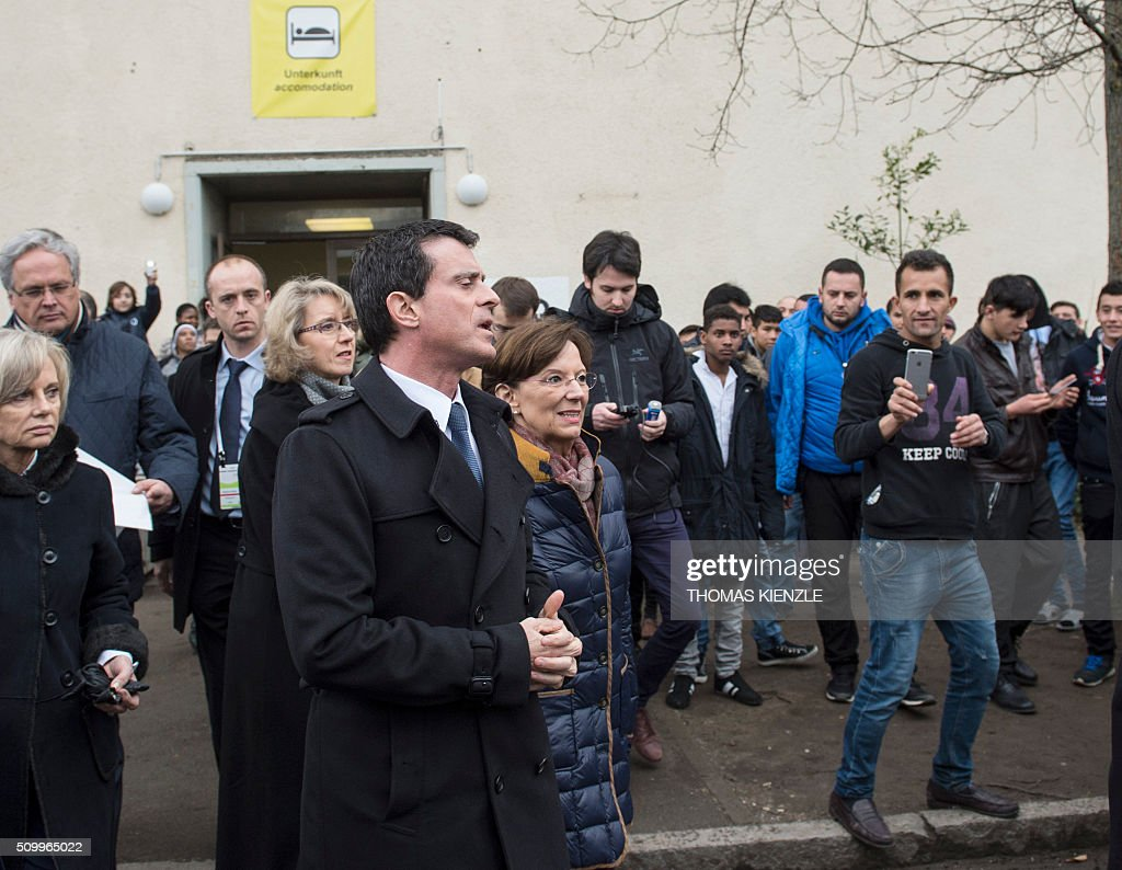 French Prime Minister Manuel Valls (front) reacts as he leaves an accomodation in the refugee camp Bayernkaserne (Bavaria barracks) in Munich, southern Germany, on February 13, 2016. / AFP / THOMAS KIENZLE