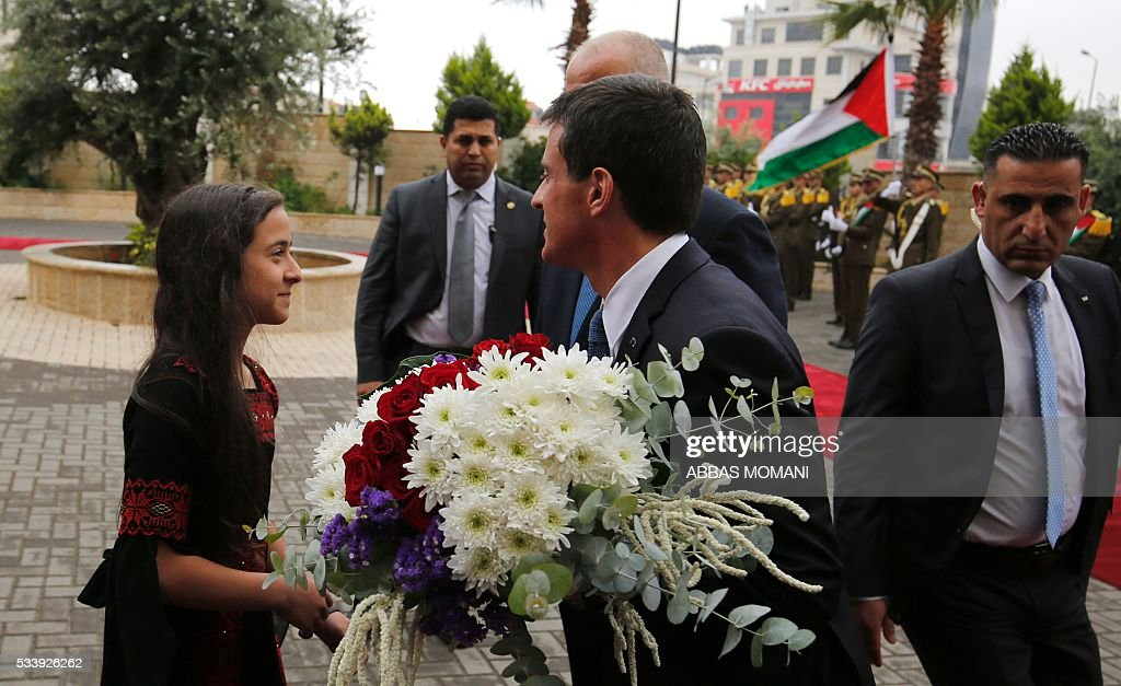 French Prime Minister Manuel Valls (C) receives a flower bouquet as he arrives with Palestinian prime minister to the West Bank city of Ramallah, on May 24, 2016. / AFP / ABBAS