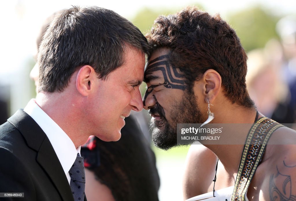 French Prime Minister Manuel Valls (L) recieves a 'Hongi', or touching of the noses, after the Wreath Laying Ceremony at the Auckland War Memorial Museum in Auckland on May 2, 2016. Valls arrived in New Zealand on May 1st after visiting the French Pacific territory of New Caledonia, with officials in his delegation confirming that he will detour to Australia later today. / AFP / MICHAEL