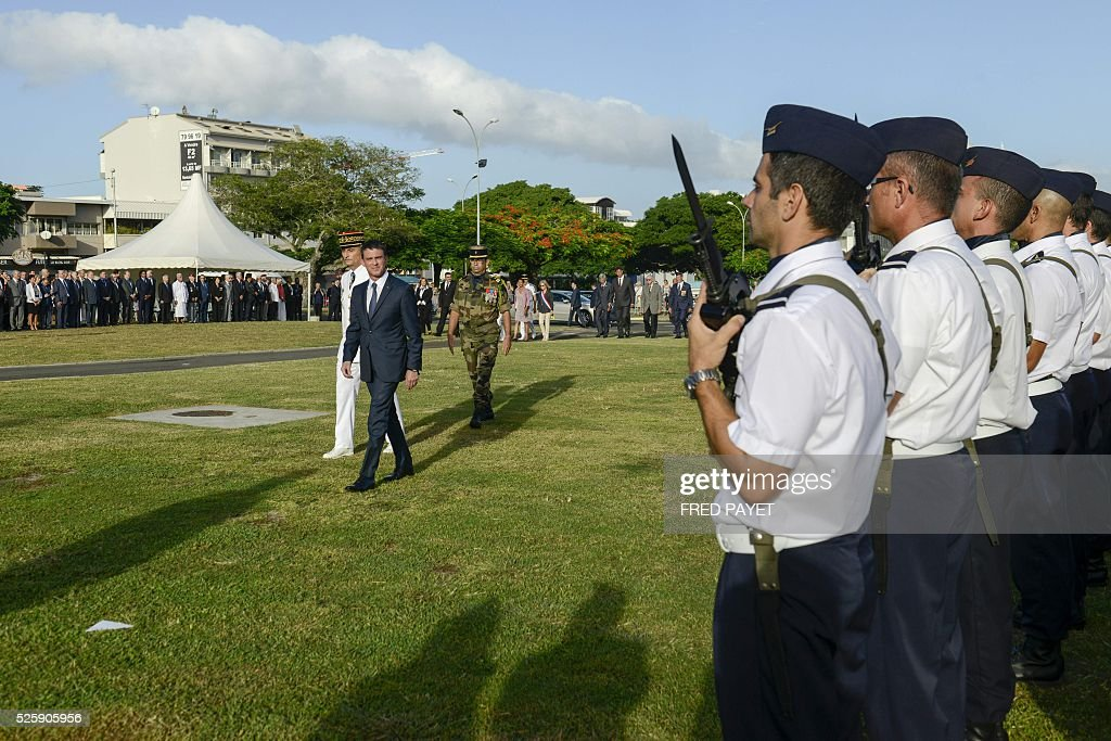 French Prime Minister Manuel Valls (C) reviews the guard of honour as he arives with French Commander of the French Armed Forces in New Caledonia, Major General Philippe Leonard (back C) at the place Bir-Hakeim in Noumea during a wreath lane ceremony at the wall memorial on April 29, 2016. / AFP / Fred Payet