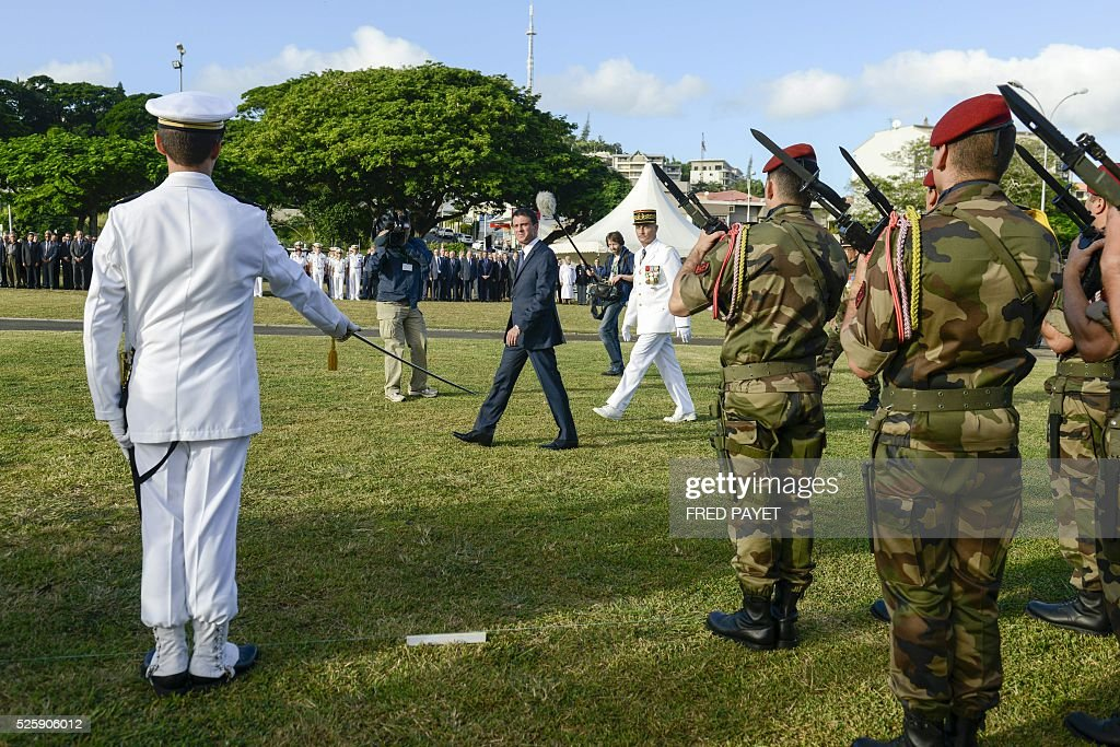 French Prime Minister Manuel Valls (L) reviews the guard of honour as he arives with French Commander of the French Armed Forces in New Caledonia, Major General Philippe Leonard (C) at the place Bir-Hakeim in Noumea during a wreath lane ceremony at the wall memorial on April 29, 2016. / AFP / Fred Payet