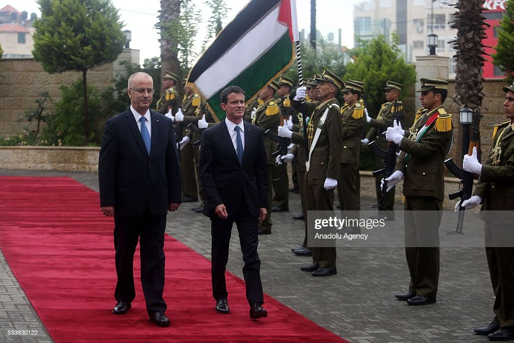 French Prime Minister Manuel Valls (R) reviews the honor guard as he is welcomed by Palestinian Prime Minister Rami Hamdallah (L) in an official welcoming ceremony at Prime Minister's Residence in Ramallah, West Bank on May 24, 2016.