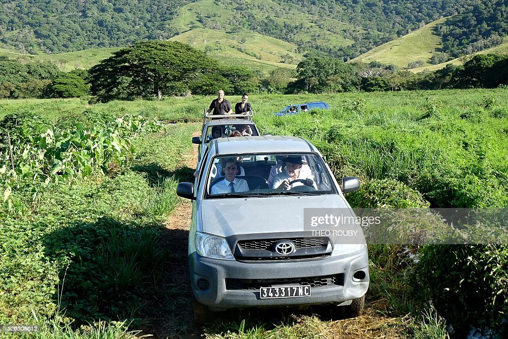 French Prime Minister Manuel Valls (L) rides in a car with Jean-Jacques Delathiere in his family on April 30, 2016 in La Foa, as part of Valls' visit to the French Pacific territory of New Caledonia. / AFP / Th��o Rouby