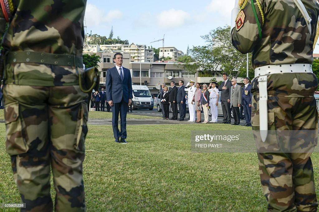 French Prime Minister Manuel Valls salutes at the place Bir-Hakeim in Noumea during a wreath lane ceremony at the wall memorial on April 29, 2016. / AFP / Fred Payet