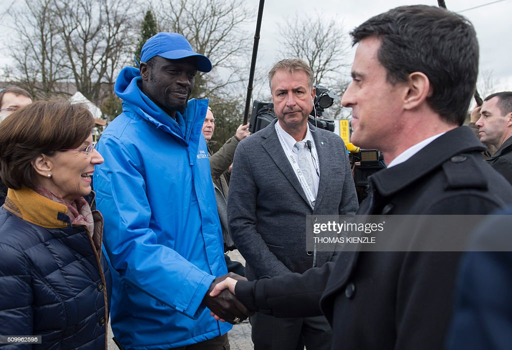 French Prime Minister Manuel Valls (R) shakes hands with a staff member of the refugee camp Bayernkaserne (Bavaria barracks) in Munich, southern Germany, on February 13, 2016. Valls visited the refugee camp during his visit in Munich for the Munich Security Conference. / AFP / THOMAS KIENZLE