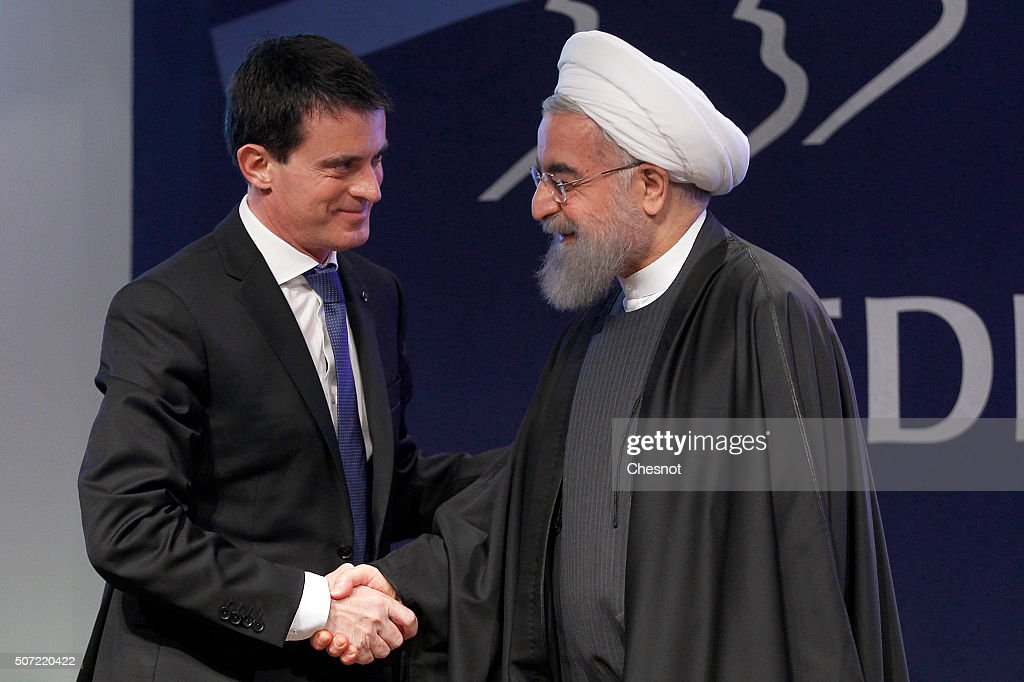 French Prime Minister Manuel Valls shakes hands with Iranian President Hassan Rouhani after a meeting at the French employers association MEDEF...