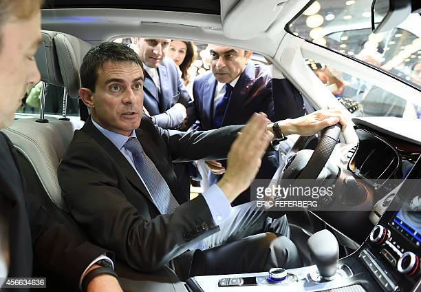 French Prime Minister Manuel Valls sits in a Renault car displayed at the 2014 Paris Auto Show and talks with Renault CEO Carlos Ghosn and Economy...