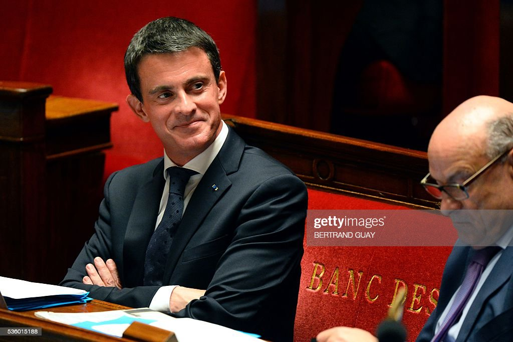 French Prime Minister Manuel Valls (L) smiles as he attends a session of questions to the Government at the French National Assembly in Paris, on May 31, 2016.