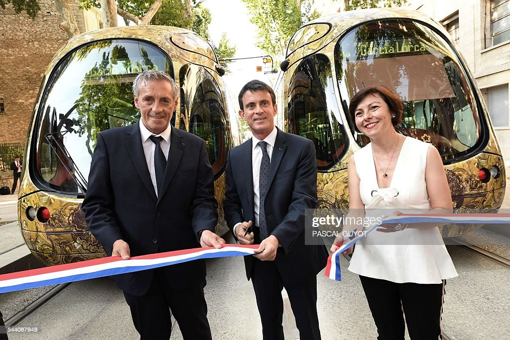 French Prime Minister Manuel Valls (C) smiles next to Mayor of Montpellier Philippe Saurel (L) and Carole Delga, president of the regional council Occitanie (R), on July 1, 2016, during the inauguration of the tram line 4 in Montpellier, southern France. / AFP / PASCAL