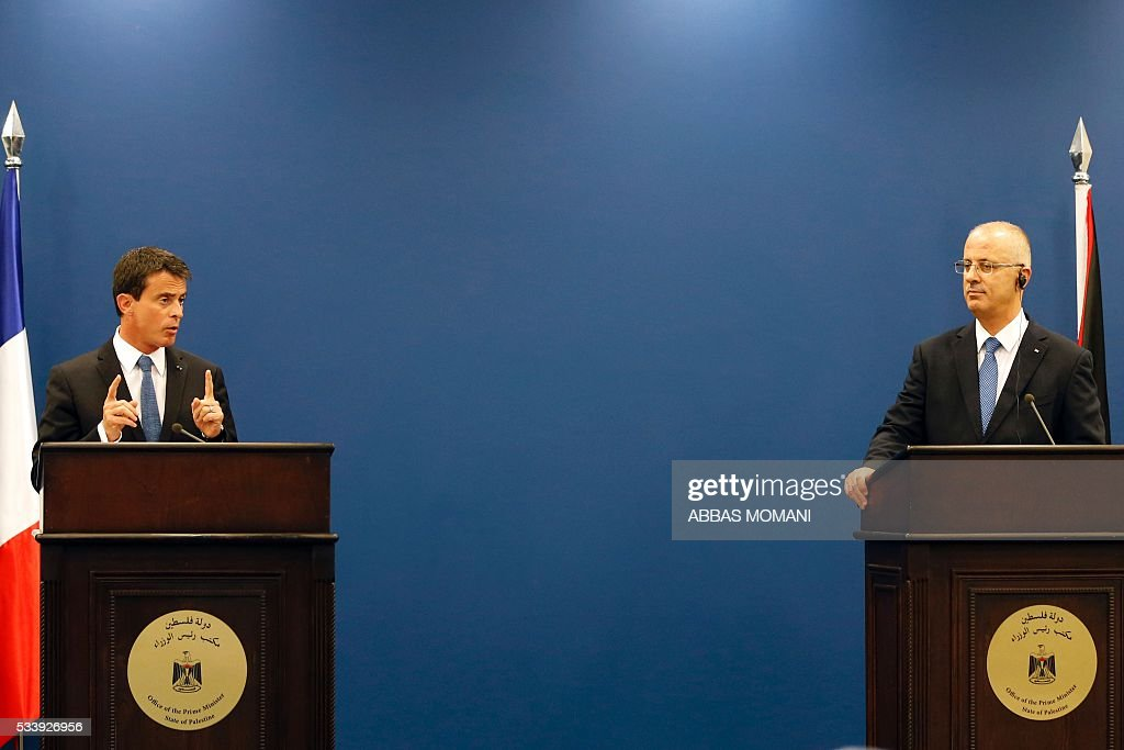 French Prime Minister Manuel Valls (L) speaks as Palestinian prime minister Rami Hamdallah listens during a press conference in the West Bank city of Ramallah, on May 24, 2016. Palestinian prime minister Rami Hamdallah dismissed an Israeli proposal for direct negotiations instead of a French multilateral peace initiative, calling it an attempt to 'buy time'. / AFP / ABBAS