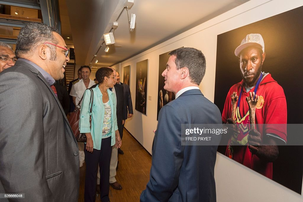 French Prime Minister Manuel Valls (R) speaks with Emmanuel Tjibaou (L), son of Kanak independentist leader Jean-Marie Tjibaou, while French Overseas Territories Minister George Pau-Langevin (C) looks at an exhibit during a visit to the Tjibaou Cultural Centre in Noumea, the French Pacific territory of New Caledonia, on May 1, 2016. / AFP / Fred Payet