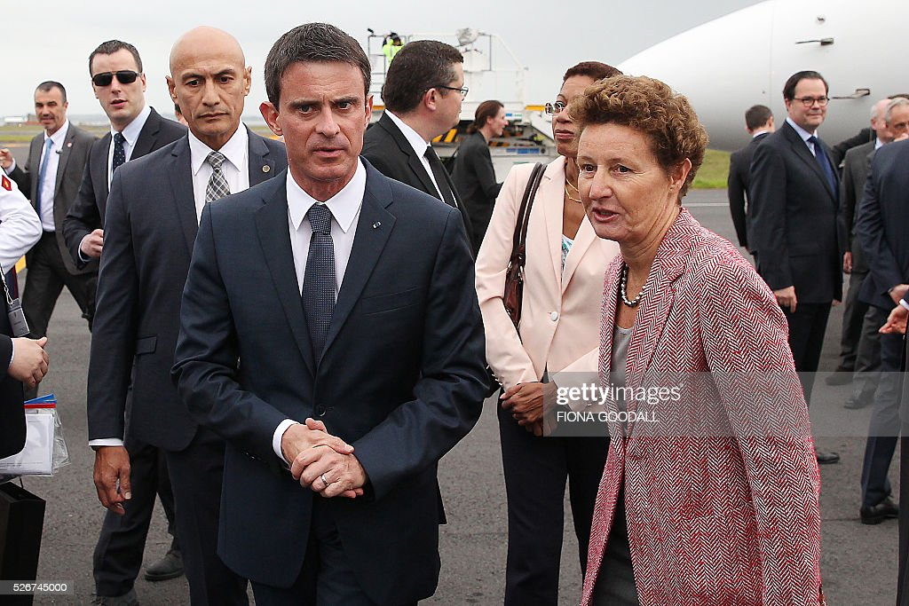 French Prime Minister Manuel Valls (front L) speaks with French Ambassador to New Zealand Florence Jeanblanc-Risler (R) as he arrives in Auckland on May 1, 2016. Valls arrived in New Zealand on May 1 after visiting the French Pacific territory of New Caledonia, with officials in his delegation confirming that he will detour to Australia on May 2. / AFP / Fiona Goodall