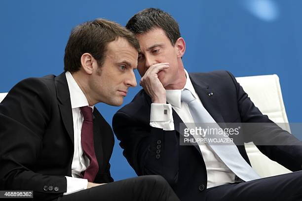 French Prime Minister Manuel Valls speaks with French Economy minister Emmanuel Macron during the presentation of a government plan to encourage...