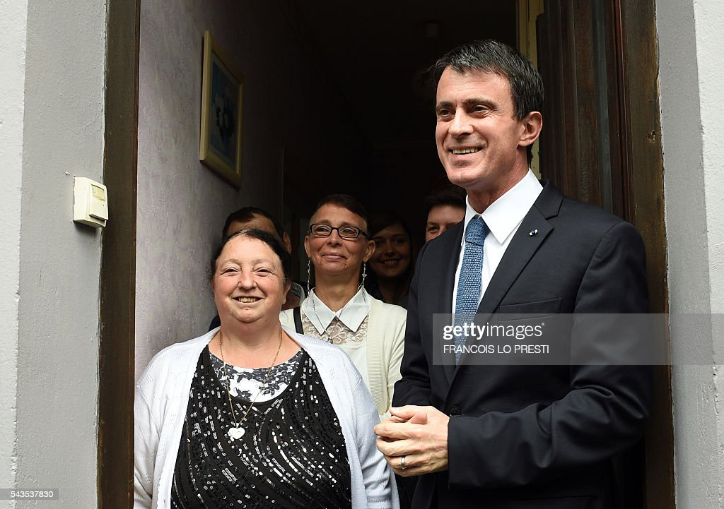 French Prime Minister Manuel Valls (R) speaks with inhabitants, during a visit to the 'Cite 9' in Lens, on June 29, 2016, dedicated to the rehabilitation of Lens-Lievin mining area and the surroundings, including the renovation of housing. French urban planner Jean-Louis Subileau is in charge of the project and is expected to report next fall. / AFP / FRANCOIS