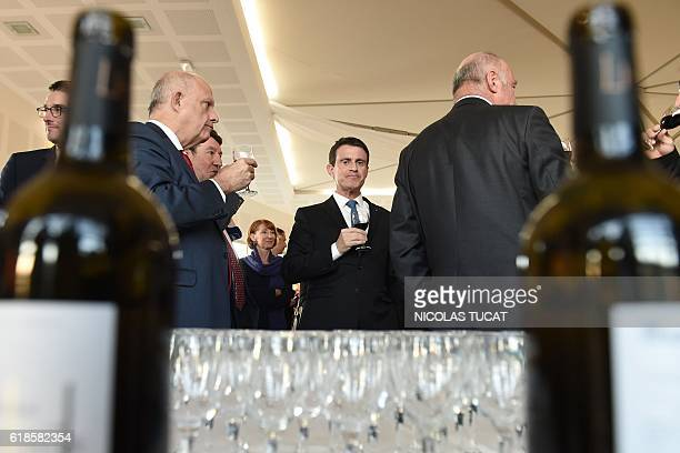 French Prime Minister Manuel Valls tastes a glass of red wine during his visit to Chateau LucheyHalde on October 27 2016 in Merignac southwestern...