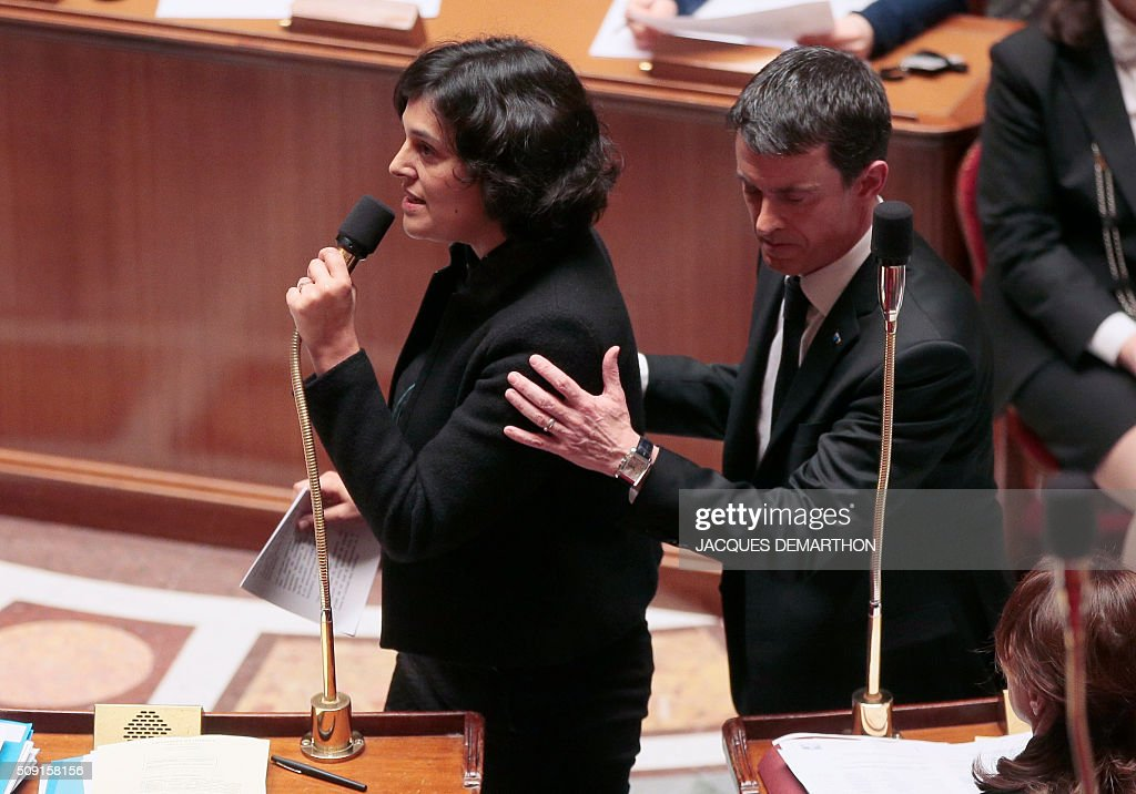 French Prime Minister Manuel Valls (R) walks past French Minister of Labour Myriam El Khomri as she speaks during a session of questions to the government at the French National Assembly in Paris on February 9, 2016. / AFP / JACQUES DEMARTHON