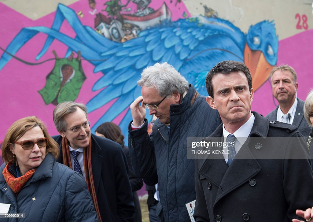 French Prime Minister Manuel Valls (R) walks through the refugee camp Bayernkaserne (Bavaria barracks) in Munich, southern Germany, on February 13, 2016. Valls visited the refugee camp during his visit in Munich for the Munich Security Conference. / AFP / THOMAS KIENZLE