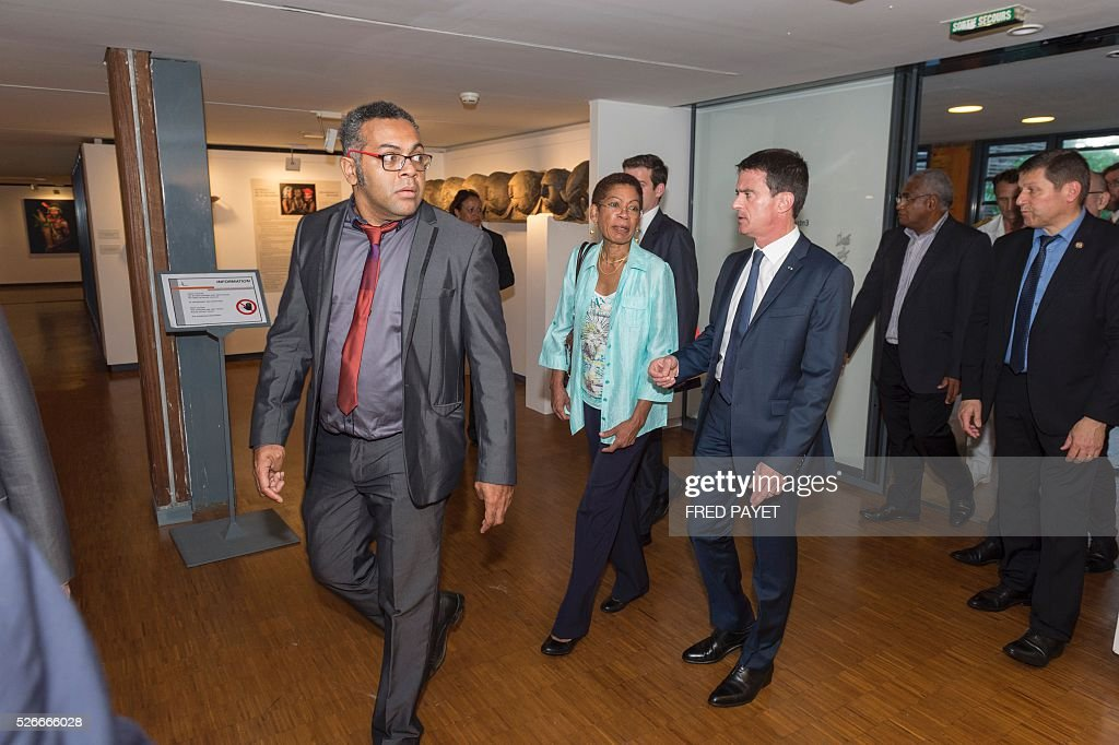 French Prime Minister Manuel Valls (centre R) walks with Emmanuel Tjibaou (L), son of Kanak independentist leader Jean-Marie Tjibaou, and French Overseas Territories Minister George Pau-Langevin (C) during a visit to the Tjibaou Cultural Centre in Noumea, the French Pacific territory of New Caledonia, on May 1, 2016. / AFP / Fred Payet