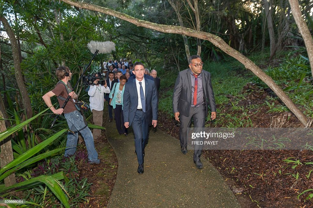 French Prime Minister Manuel Valls (L) walks with Emmanuel Tjibaou (R), son of Kanak independentist leader Jean-Marie Tjibaou, during a visit to the Tjibaou Cultural Centre in Noumea, the French Pacific territory of New Caledonia, on May 1, 2016. / AFP / Fred Payet