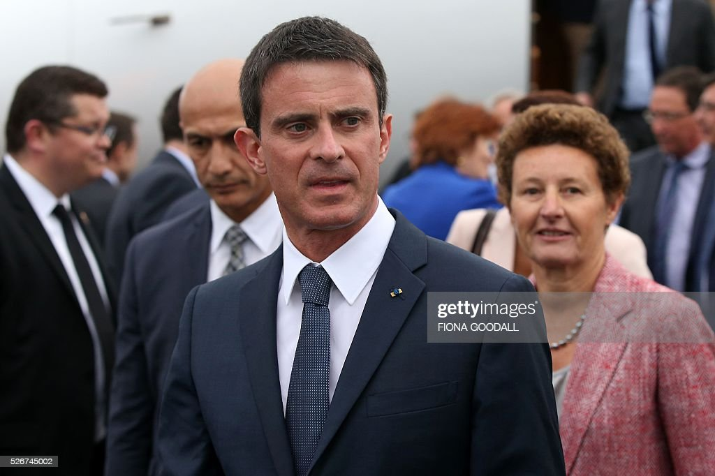 French Prime Minister Manuel Valls (front) walks with French Ambassador to New Zealand Florence Jeanblanc-Risler (R) as he arrives in Auckland on May 1, 2016. Valls arrived in New Zealand on May 1 after visiting the French Pacific territory of New Caledonia, with officials in his delegation confirming that he will detour to Australia on May 2. / AFP / Fiona Goodall