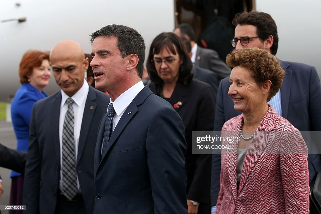 French Prime Minister Manuel Valls (2nd L) walks with French Ambassador to New Zealand Florence Jeanblanc-Risler (R) as he arrives in Auckland on May 1, 2016. Valls arrived in New Zealand on May 1 after visiting the French Pacific territory of New Caledonia, with officials in his delegation confirming that he will detour to Australia on May 2. / AFP / Fiona Goodall