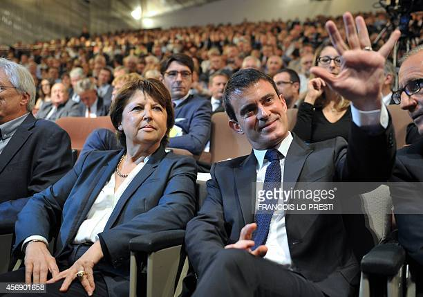 French Prime minister Manuel Valls waves eyed by Lille's mayor Martine Aubry prior to attend the 25th anniversary of the national convention of...