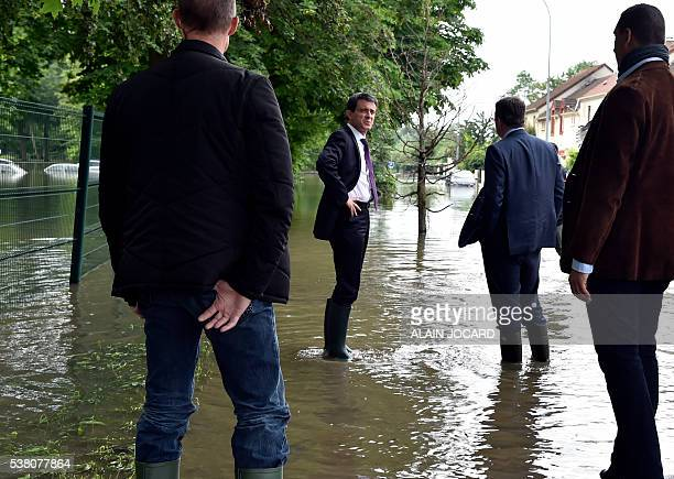French Prime Minister Manuel Valls wearing boots and flanked by French President of the Essonne Departmental Council Francois Duvovray visits flooded...